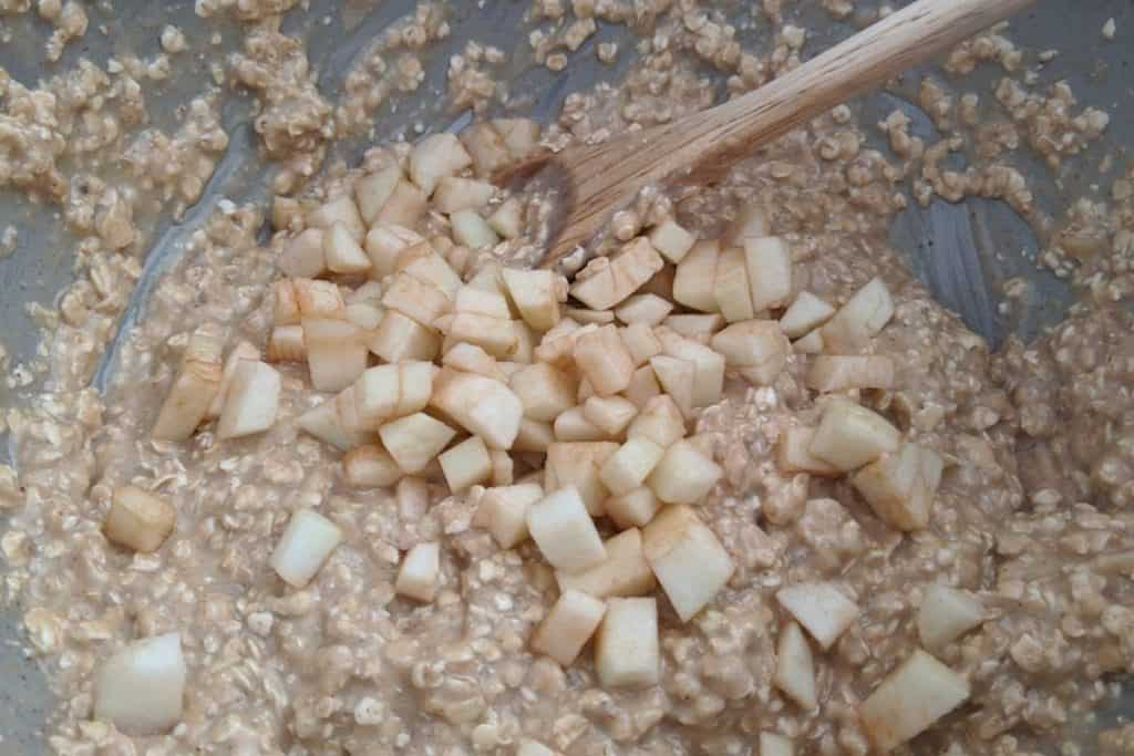 Stirring diced apples into oatmeal batter to make kidney healthy oatmeal cookies.