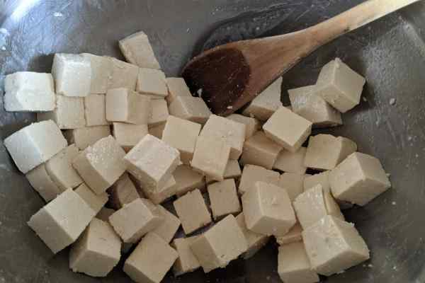 Raw tofu cubes mixed with oil in a stainless bowl.