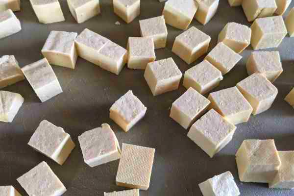 Raw tofu cut into cubes ready for seasoning.