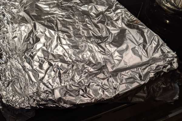 Red peppers cooling under aluminium foil to remove the skin when cooled.