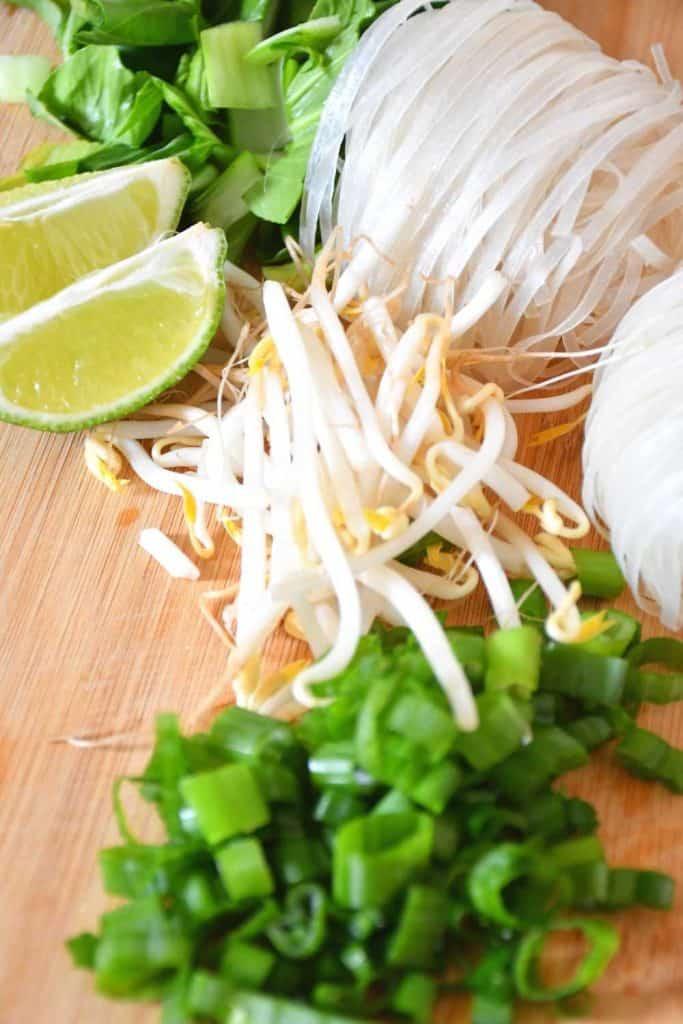 Quartiers de lime, oignons verts hachés, germes de soja et nouilles de riz sèches pour le pho végétalien faible en sodium.