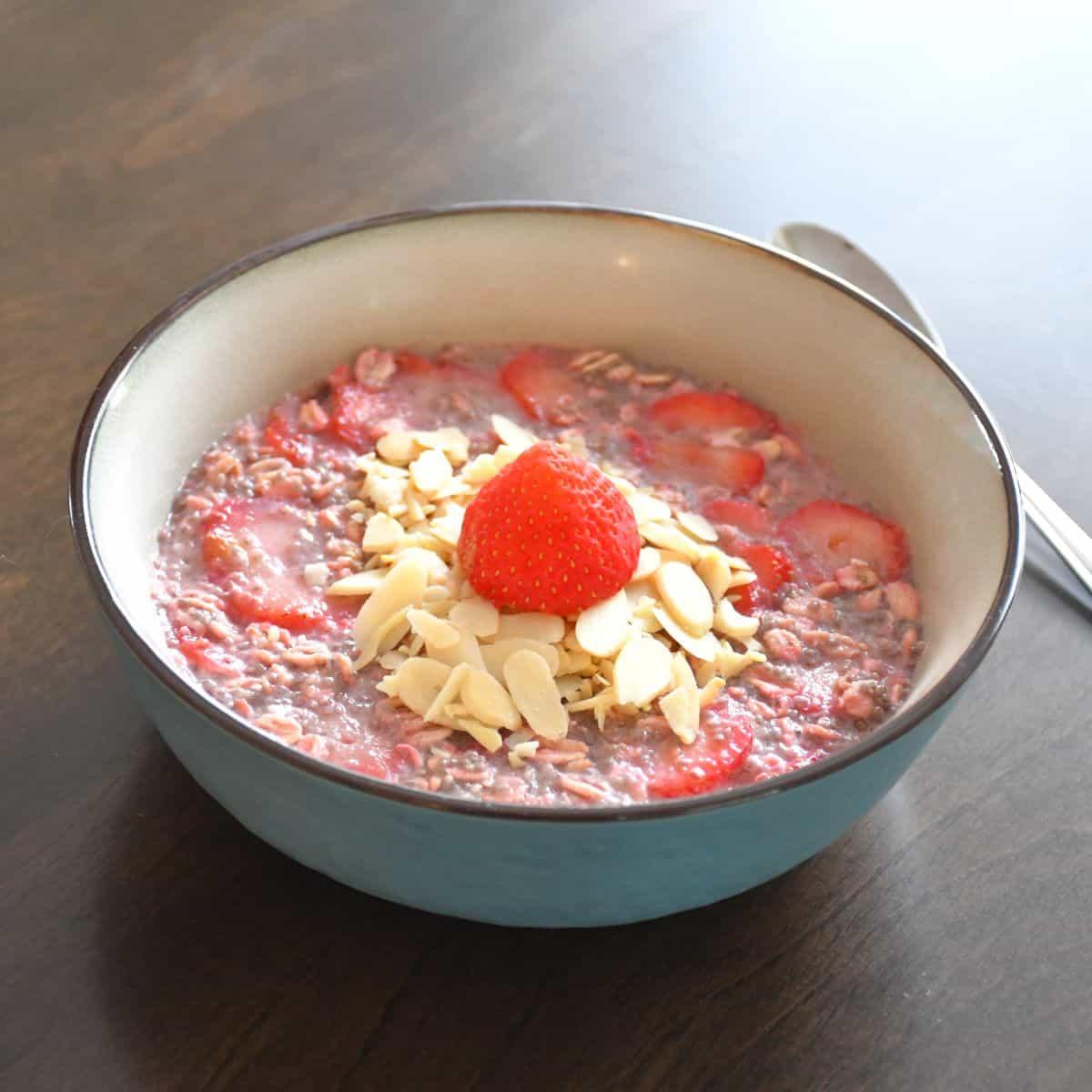 Gros plan sur le résultat final du gruau overnight aux fraises garnie d'amandes tranchées et d'une fraise fraîche dans un bol en céramique bleu.