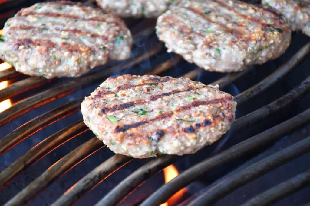 Cilantro pork burger patties cooking on the grill at medium-high heat.
